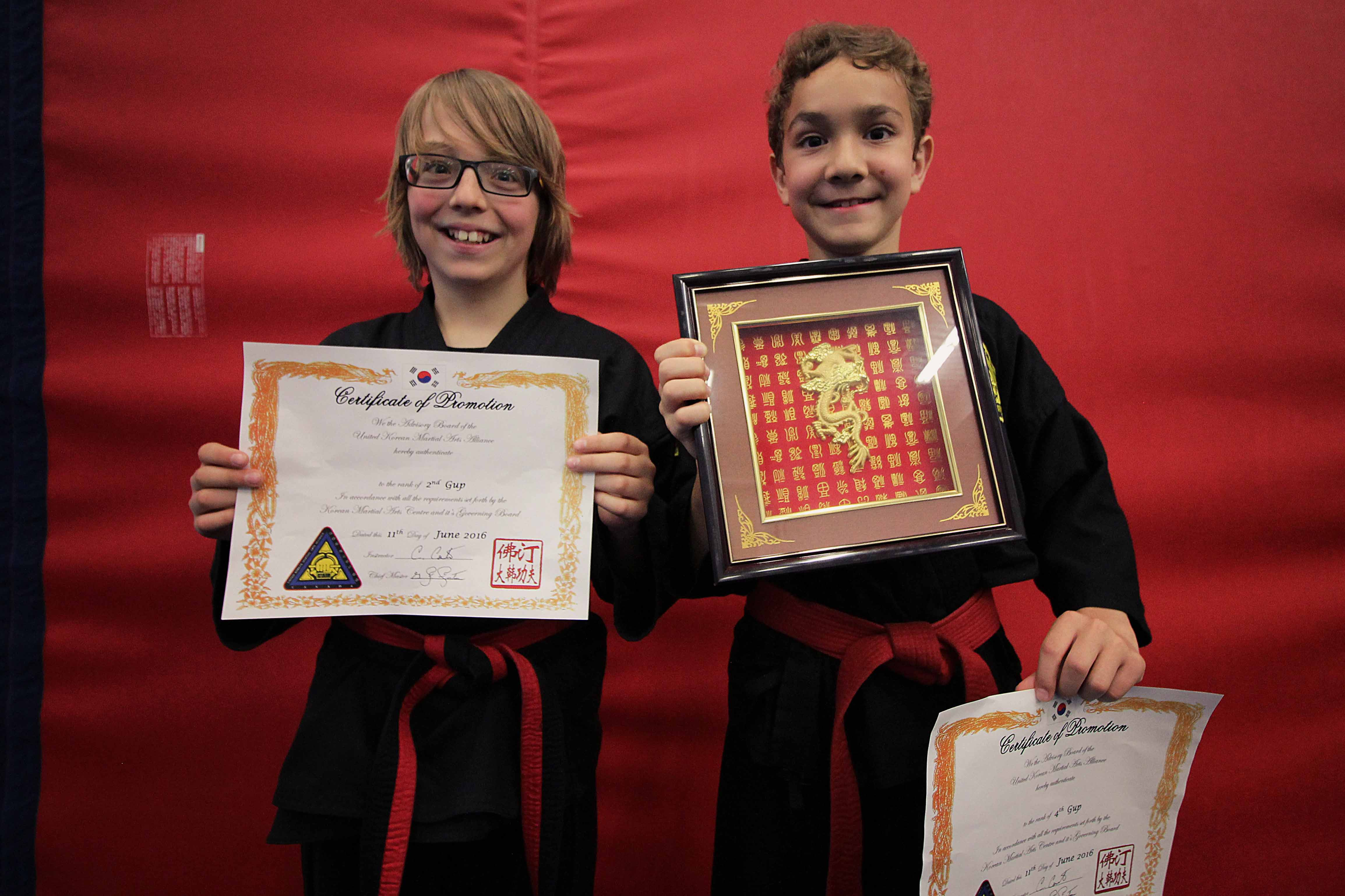 Two Valley KMAC students showing off their tournament awards and promotions.